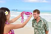 pic of hawaiian girl  - Hawaii woman giving lei garland of pink orchids welcoming tourist on Hawaiian beach - JPG