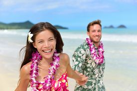 pic of traditional  - Happy Hawaii beach holiday couple in Aloha shirt and dress and wearing Hawaiian flower leis as a Polynesian culture tradition for welcoming tourists or for a wedding or honeymoon vacation - JPG