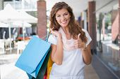 Portrait of smiling woman with shopping bags looking at camera and showing thumbs up at the shopping poster