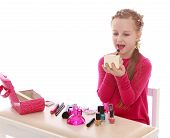 pic of little school girl  - little girl of school age in a red dress sitting at a table and lipstick - JPG