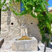 pic of stone house  - Public tap water device on the facade covered a green wild vine of the old stone house in beautiful medieval village Vaison la Romaine on hot summer day - JPG