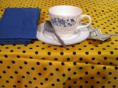 stock photo of poka dot  - a coffee cup and tip on a poka dot table cloth - JPG