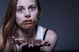 image of bulimic  - Bulimic girl eating chocolate snack with obsession - JPG