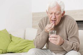 stock photo of hypertensive  - Ill senior man taking medicine for hypertension - JPG