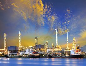 stock photo of fuel tanker  - tanker ship and petrochemical oil refinery industry plant with beuatiful lighting against dusky sky use for heavy industrial and energy fuel business - JPG