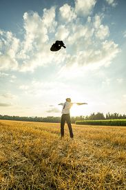 picture of stressless  - Successful Young Businessman in an Open Field Throwing his Coat in the Air with Arms Wide Open Against Sunlight - JPG