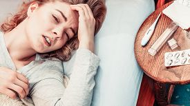 stock photo of laying-in-bed  - Sick woman suffering from headache pain - JPG
