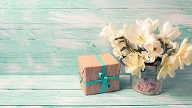 pic of text-box  - Background with colorful narcissus flowers and box with present on turquoise painted wooden planks - JPG