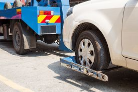 pic of towing  - Tow truck towing a broken down car with focus on car being towed - JPG