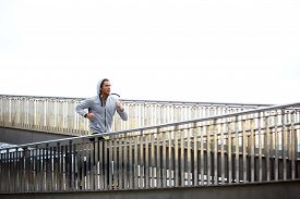 picture of bridge  - Sporty young man run up the bridge with overcast sky on background - JPG