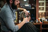 Bearded coiffeur cutting hairstyle by scissors  poster