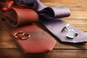 Wedding rings and cuff-links on ties, closeup poster