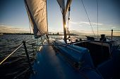 Sunset At The Sailboat Deck While Cruising Sailing At Opened Sea Or River. Yacht With Full Sails Up  poster