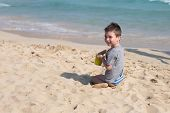 Young Boy Face. Kid Playing With Sand On The Beach Alone. Little Boy Near Sea. Summer Play. poster