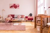 Flowers On Wooden Table In Pink Apartment Interior With Sofa Under Poster Next To Cabinet. Real Phot poster
