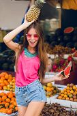 Summer Tropical Girl In Pink Sunglasses On Market On Fruits Background. She Holds Ananas On Head And poster