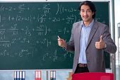 Young handsome math teacher in classroom  poster
