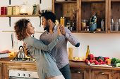 Happy Moments. Young African-american Couple In Love Dancing In Kitchen, Copy Space poster