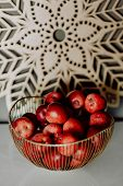 Fresh red apples in a brass basket on a white table poster