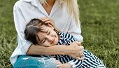 Lovely Image Of Cute Little Child Girl Lying On Her Mothers Legs Outside. Loving Mother And Daughte poster