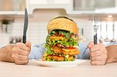 Young Hungry Man With Cutlery Eating Huge Burger At Table poster