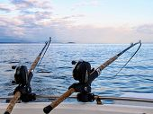 Two Fishing Rods Held In Fishing Rod Holders, Attached To A Back Of A Boat.  The Rods Are Bent From  poster