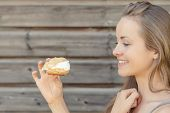 Happy Summertime. Young Beautiful And Smiling Woman In Garden With A Sweet Pastry. poster