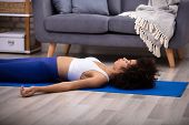 Athletic Young Woman Lying On Blue Yoga Mat Over The Hardwood Floor poster