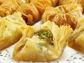 stock photo of phyllo dough  - A sweet pastry made of layered phyllo dough honey and chopped pistachios and walnuts - JPG