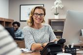 Mature beautiful woman at creative office and looking at camera. Portrait of receptionist working on poster