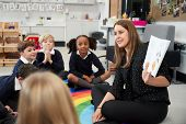 Primary school children sitting on the floor in the classroom with their teacher holding up a book t poster