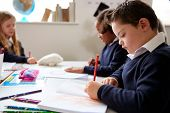 Pre-teen school boy with Down syndrome sitting at a desk writing in a primary school class, close up poster
