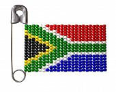 stock photo of zulu  - A safety pin with a traditional zulu beaded brooch depicting the south african flag on an isolated background - JPG