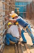 foto of formwork  - Authentic construction builders working together for positioning concrete formwork frames in place - JPG