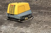 stock photo of vibrator  - Vibrating compactor soil with remote control via radio - JPG