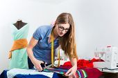 Freelancer - Fashion designer or Tailor working on a design or draft and cutting fabrics with scisso
