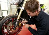 Teenager in professional training, repairing motorbike