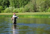 pic of fly rod  - Fisherman catches of chub fly fishing in the Chusovaya river in the afternoon - JPG