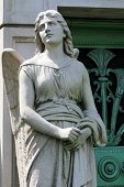 picture of mausoleum  - A stone statue of a young female angel guards the green weathered door to a mausoleum at a cemetery in Chicago - JPG