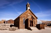 stock photo of shacks  - Old weathered wooden church in ghost town - JPG