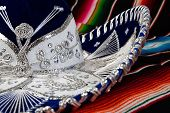 stock photo of sombrero  - Silver and white mexican sombrero with elaborate pattern on a colorful serape blanket - JPG