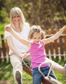 foto of seesaw  - Mother and daughter ride seesaw together - JPG