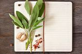 stock photo of spice  - Open recipe book with sage and spices on a wooden background - JPG