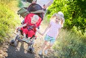 stock photo of three sisters  - little sister holding the hand with her little sibling in a stroller