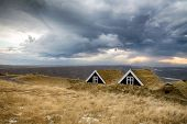 stock photo of iceland farm  - Iceland historic turf houses against a stormy sky - JPG