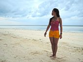 stock photo of filipina  - Filipina on a white sand beach after the storm - JPG