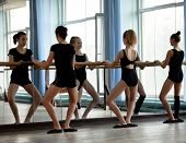 stock photo of ballet barre  - Three ballet dancers warming up before practice starts - JPG