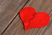 image of heartbreak  - Broken heart and thread on wooden background - JPG
