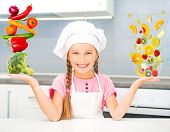 Постер, плакат: little girl dressed as a cook balanced pyramid of vegetables and fruits