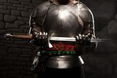 stock photo of wall-stone  - Closeup portrait of medieval knight in armor holding a sword in dark stone wall background - JPG